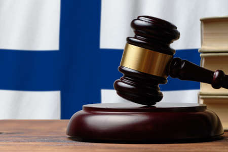 Justice and court concept in Republic of Finland. Judge hammer on a flag background.