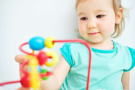 Portrait of a happy caucasian child lying playing with a metal toy. Standard-Bild