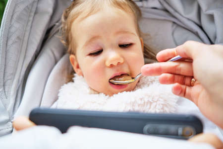 Portrait of a happy caucasian child sitting in a pram and eating food from a spoon. Standard-Bild