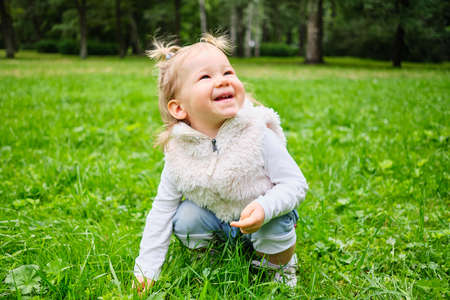 The child is joyful sitting in the grass in the park.