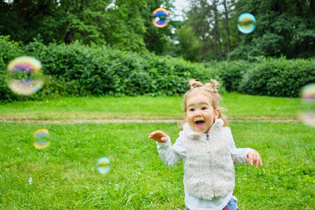 Child joyful behind soap bubbles in the park in summer.