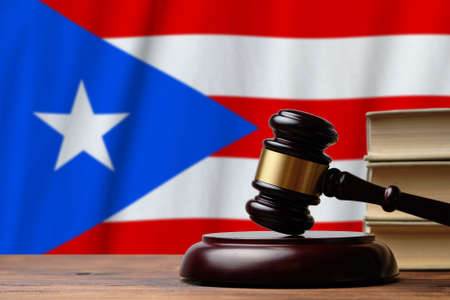 Justice and court concept in Commonwealth of Puerto Rico. Judge hammer on a flag background.
