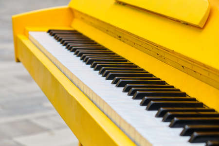 Classic yellow piano on the street close up
