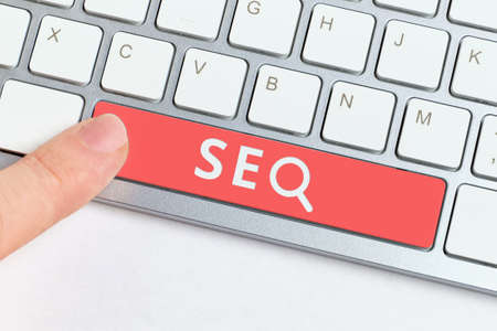 search engine optimization concept with keyboard and finger pressing. Stock Photo