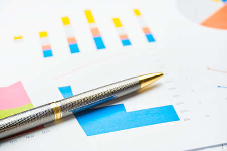 Stylish business pen on paper charts and reports.