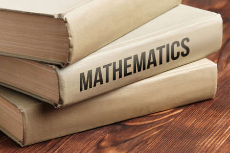 Mathematics subject book concept on a wooden table for learning