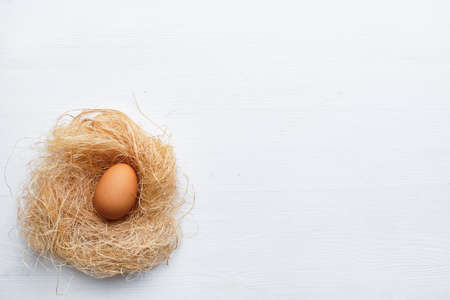 Egg in a nest made of dried grass and twigs on a wooden table. Happy easter concept. Copy space 스톡 콘텐츠