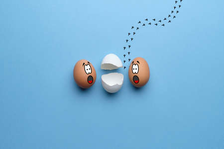 Abstract eggs with a surprised face stare at chicken escaped from an egg. Traces in the background. Happy easter concept. Top view 스톡 콘텐츠