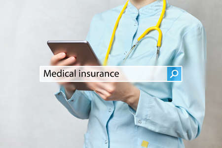 concept Medical insurance in the search bar on the background of a doctor with tablet.