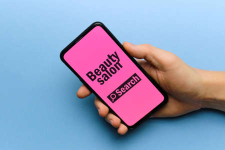 Person holding smartphone in hand with beauty salon search concept.