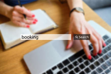 concept booking in the search bar on the background of a businesswoman with a laptop