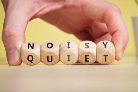 Concept of antonym noisy and quiet on wooden blocks.