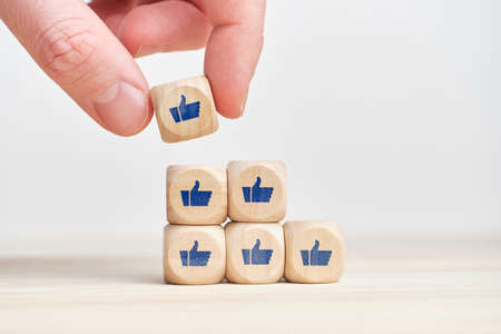 The concept of increasing popularity. Development of awareness. Cubes with thumbs up and likes