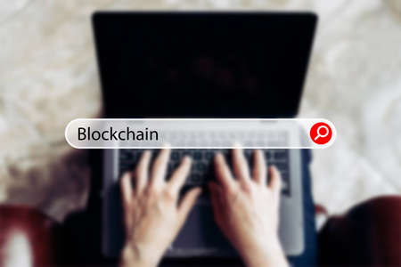 concept blockchain in the search bar on the background of a businessman with a laptop