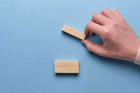 Businessman lays out wooden blocks with inscriptions step by step.