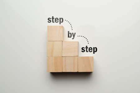 Wooden cubes in the shape of a staircase with an abstract staircase step by step.