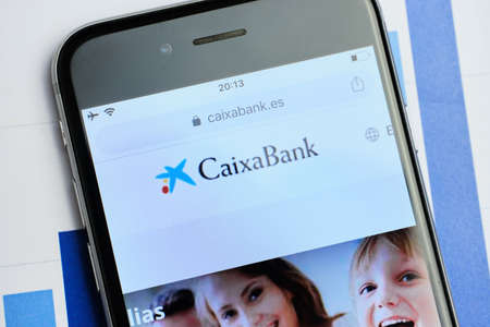 russia, st.petersburg, 14 February 2021 logo CaixaBank on the website screen through a magnifier. Close up.