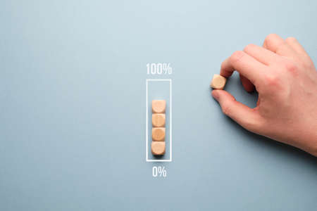 Zero to 100 percent loading bar concept with wooden cubes