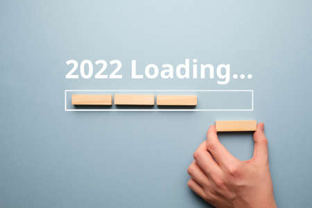 Hand folds from wooden blocks concept of loading new year 2022