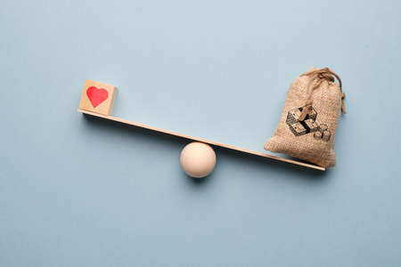 Heart as a symbol of love with a bag of money on the scales. Wealth priority.