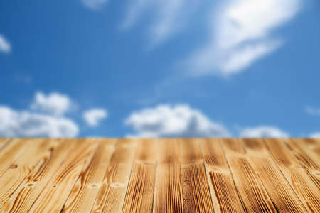 Wooden table with a blurry background of the sky with clouds. 스톡 콘텐츠