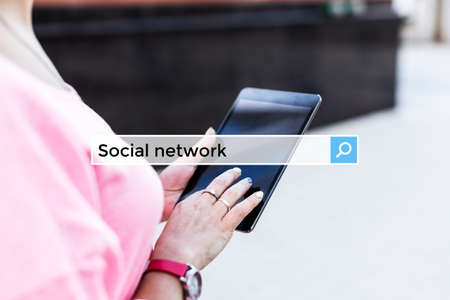 Social network in the search bar on the background girl with a tablet.