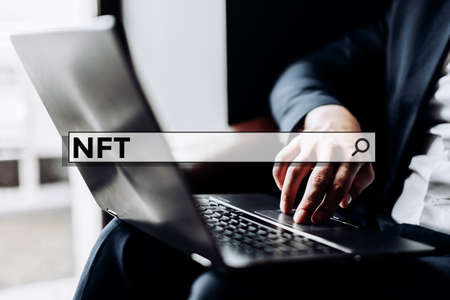 cryptographic non-fungible tokens NFT in the search bar on the background businessman with laptop.