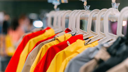 autumn-spring jackets of different colors hang on a hanger in the store.