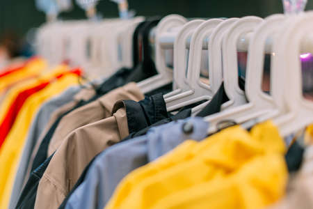 Interseasonal nylon jackets in different colors are hanging on a hanger in the store.