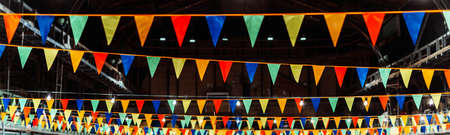 Triangular multi-colored festive ribbons stretched in the hall.