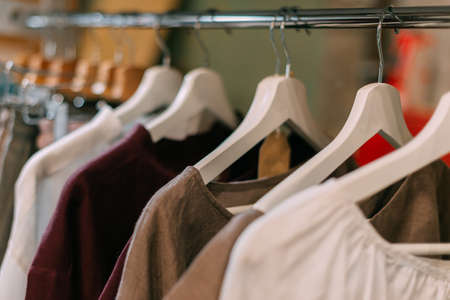 Crafted rustic linen clothes hanging on hangers in the store.