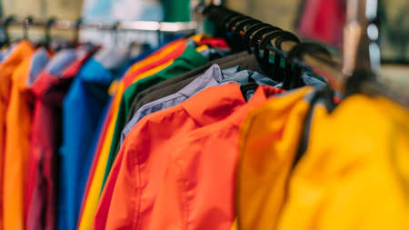 Multicolored rain jackets hang on hangers in the store.