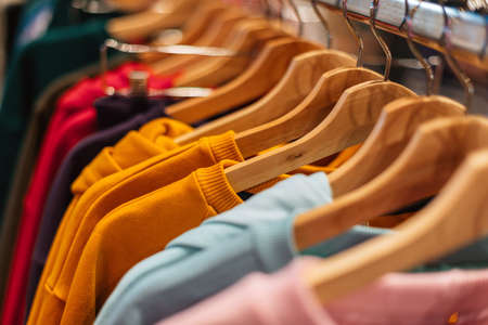 Multicolored cotton sweaters hang on hangers in the store.