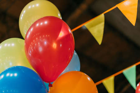 Multicolored balloons on the background of festive triangular ribbons. 写真素材