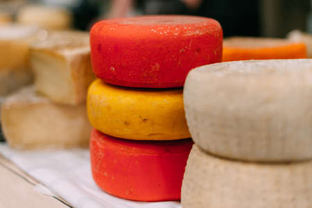 Large ready-made pieces of handmade cheese on the counter. 写真素材