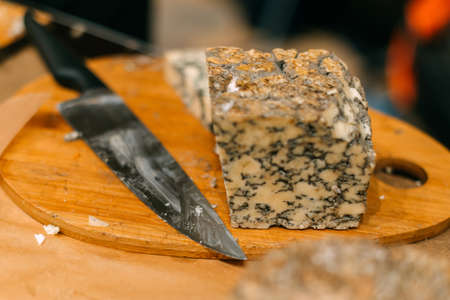 Handmade blue cheese chunks on the sample counter next to the knife. 写真素材