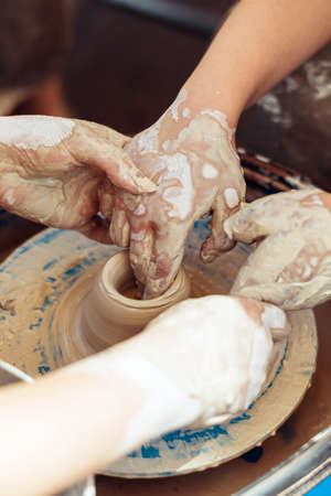 The master helps the student to create a figure in pottery