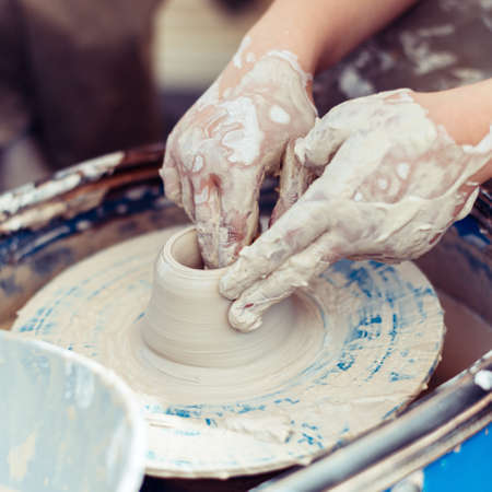 Master of pottery creates shapes from clay.