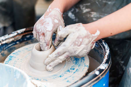Business for the production of clay dishes in pottery with the hands of a person in business.