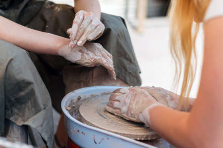 Two persons work in pottery to create figures. 写真素材