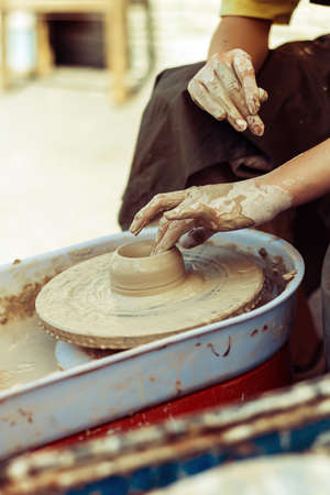 Pottery master makes dishes on the street.
