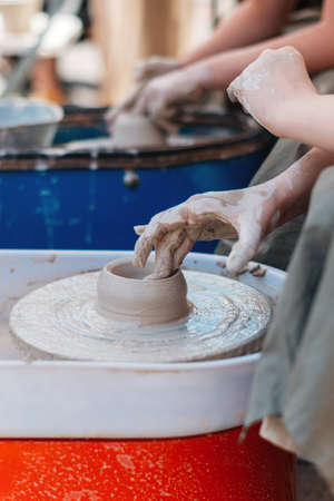 The hand of a person creates a clay figure in pottery.