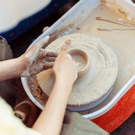 The hands of a master potter create a shape like a mug.