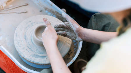 Persona neatly makes a clay figure in pottery.
