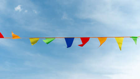 Festive ribbon made of multicolored triangles on the background of the sky.