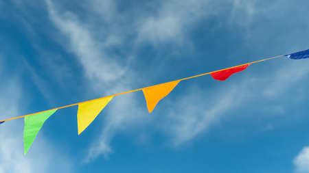 Colored triangles on a ribbon soar in the air against the sky.