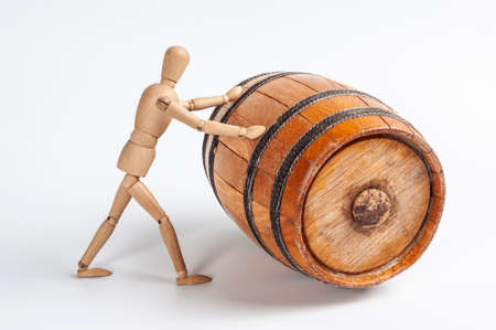 Wooden man rolls an old oak cask of wine closed by a cork. On a white background. Winemaking and logistics concepts.