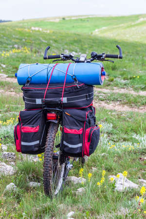 A lone mountain bike with a backpack stands on a hilly terrain. A concept of cycling travel. Equipment for cycling tourism.
