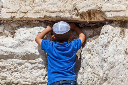 A little Jewish boy prays at the Western wall in Jerusalem. Notes with prayers and wishes in the crack between the stones.