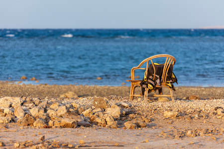 A lonely old chair stands on a rocky seashore. Selective focus.